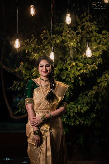 Bride wearing a gold saree with a bottle green blouse.