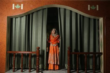 Photo of Bride in an orange suit with flared pants