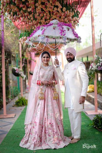 Bride posing with father under an umbrella phoolon ki chaadar.