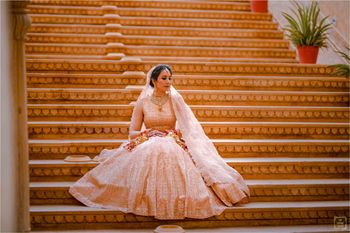 Photo of Bride dressed in a blush pink lehenga.