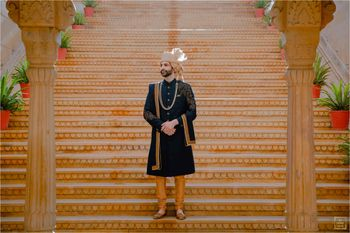 Groom wearing a navy blue sherwani with gold churidars and a beige safa.