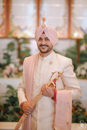 Groom wearing ivory sherwani with pink turban and stole.