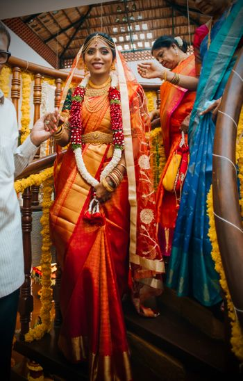 Photo of South Indian bride in a red and gold saree.