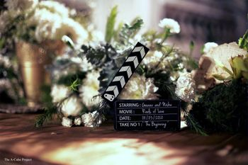 Photo of Clapper boards and flowers used as a table centerpiece.