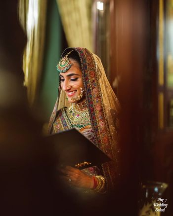 Photo of statement bridal nath with pretty maangtikka and necklace with sabyasachi lehenga