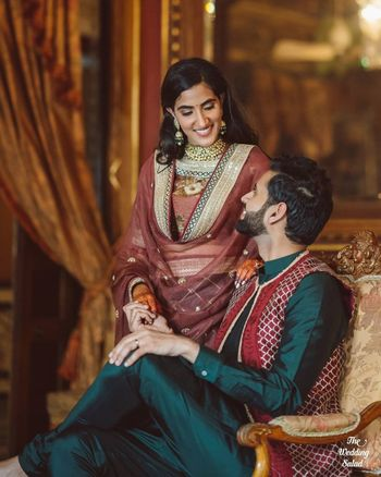 Photo of matching bride and groom in outfits for the mehendi
