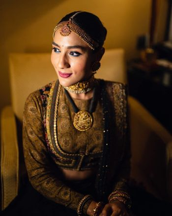 Photo of Bride wearing a jacket style blouse with her lehenga.