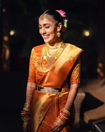 Photo of A happy bride dressed in a gold kanjeevaram.