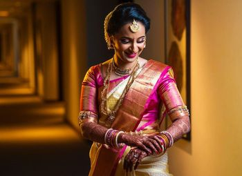 South Indian bride in an off white and pink saree.