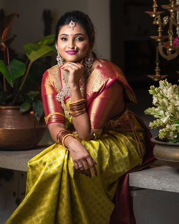 South Indian bride wearing a green saree with a molten red blouse.