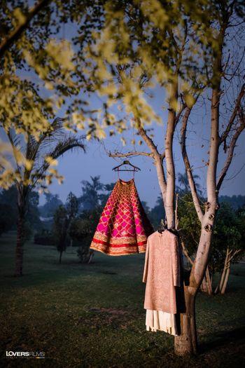 lehenga and sherwani on hanger on a tree