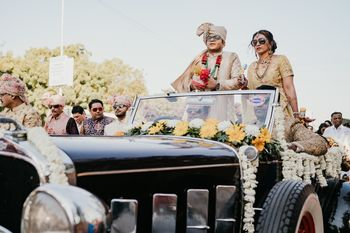 groom entering with his mother in a vintage car