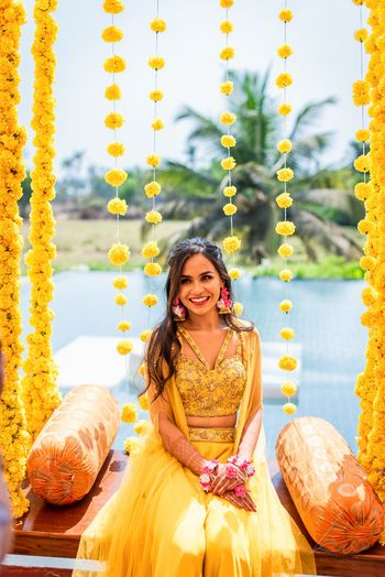 Bride in a yellow cape set sitting on a jhoola.