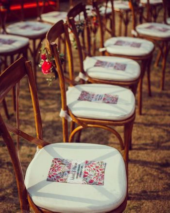 Photo of wedding programs placed on chairs for outdoor wedding