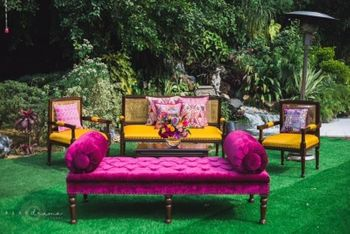 Photo of funky decor elements for mehendi with a fuchsia sofa