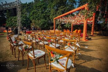 Photo of simple orange mandap with chair decor for intimate wedding