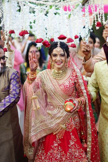 Photo of Bridal entry under a phoolon ki chaadar.