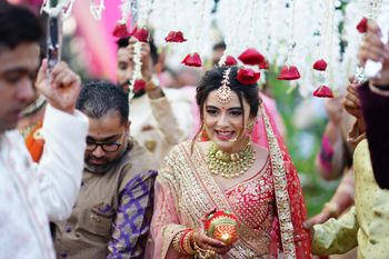 Bride entering under a phoolon ki chaadar.