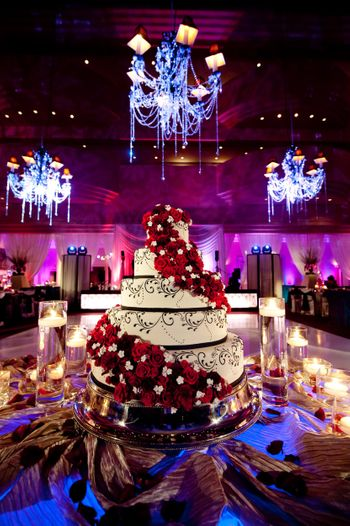 Five-tier wedding cake with flower arrangement.
