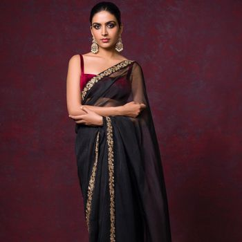 Black saree with a maroon velvet blouse.