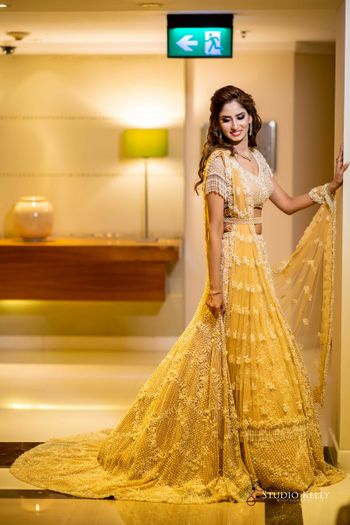 Bride wearing a yellow lehenga with a tasseled blouse.