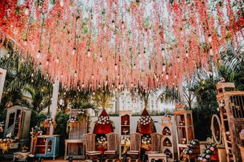 Ceiling decor done with pink wisteria and suspended bulbs.