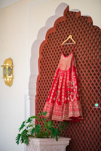 red bridal lehenga on a hanger in the room