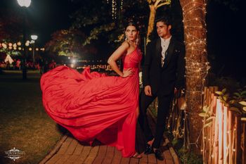 Bride and groom color-contrasting in red and black outfits.
