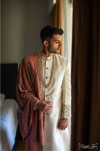 Groom wearing an ivory sherwani with a dusty pink stole.