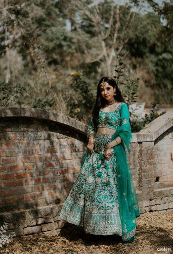 Bride wearing teal green lehenga.