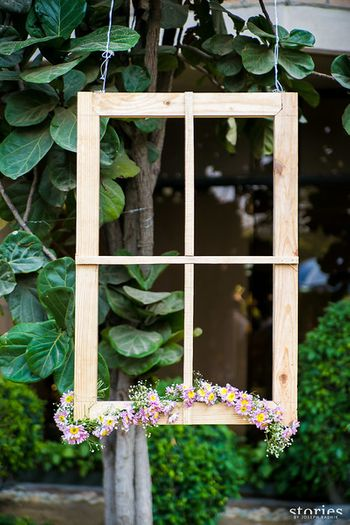 Photo of rustic wooden frames with flowers hanging for photobooth