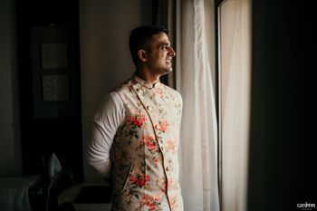 Groom wearing a floral nehru jacket with kurta-pyjama.