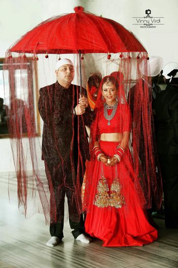 Photo of Bride in Monotone Red Lehenga Entering under Umbrella
