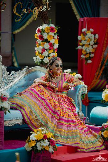 Bide wearing multi-coloured lehenga on mehendi.
