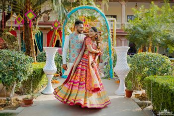 Bride and groom dressed in vibrant outfits.