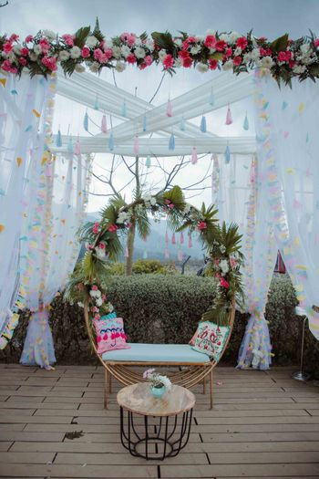 A floral wreath seating with a backdrop featuring white curtains .
