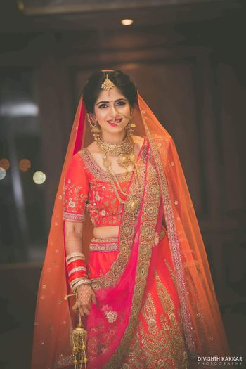 Bride in Orange Pink and Red Lehenga