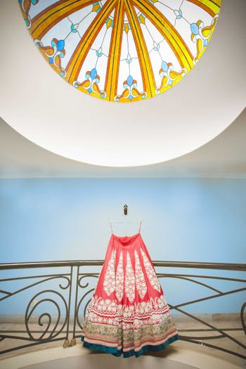 Photo of Red Bridal Lehenga with Blue Border on Hanger