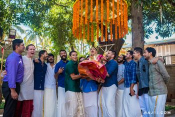 Photo of South indian wedding with Groomsmen picking bride