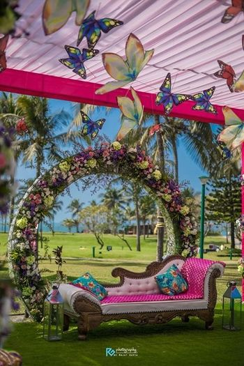 Floral wreath seating with hug flower and butterfly hangings.