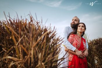 Bride and groom posing amidst green fields.