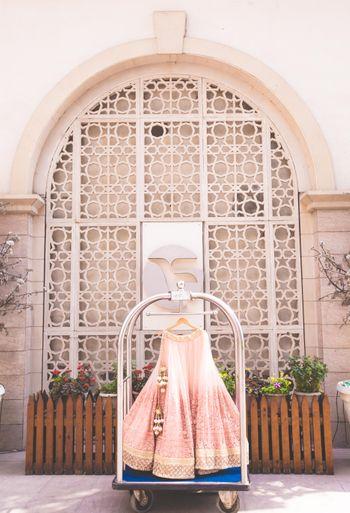 Light pink lehenga on hanger in hotel luggage cart
