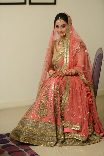 Photo of Peach and gold bridal lehenga with thread work