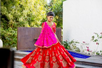 Twirling bride in red and pink lehenga