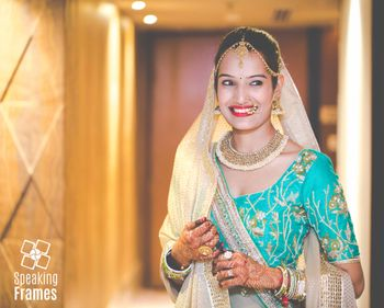Photo of Bride in Aqua Lehenga with gold motifs