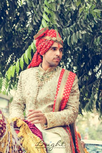 Off white and red embroidered sherwani with jewellery