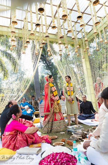 Mandap with hanging flower strings and temple bells