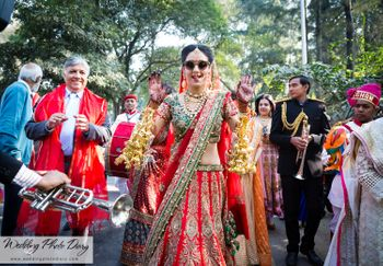 Bride in red and green lehenga wearing sunglasses