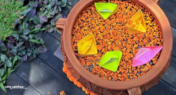 Earthen pot with floating petals and paper boats