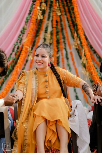 Bride wearing a simple yellow suit for mehendi